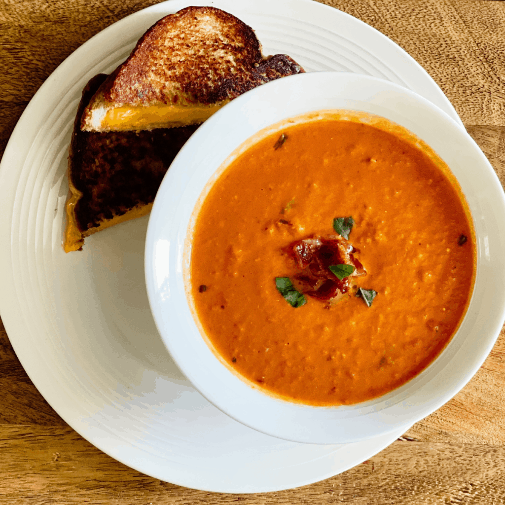 Arial view of a bowl of tomato soup and grilled cheese on a wooden board